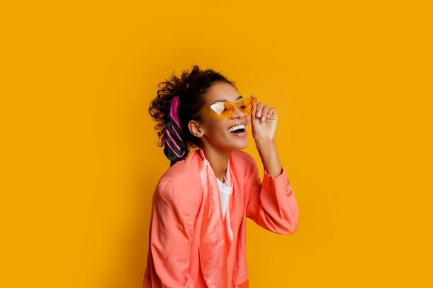 Linda garota africana no casaco rosa posando com expressão de rosto feliz sobre fundo amarelo.