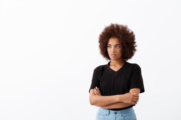 Linda garota africana pensando sobre parede de luz.