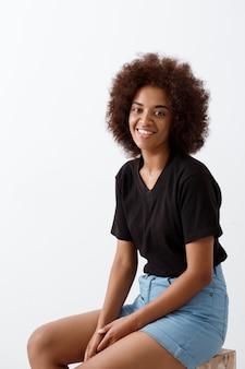 Linda garota africana sentado e sorrindo sobre parede de luz.