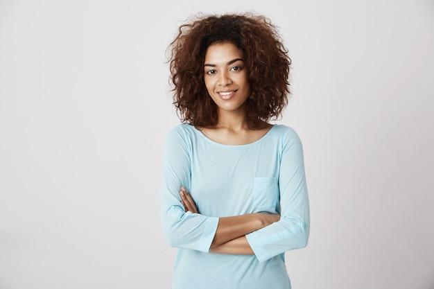 Linda garota africana sorrindo posando com braços cruzados.