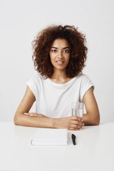 Linda garota africana sorrindo sentado à mesa sobre parede branca.