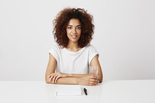 Linda garota africana sorrindo sentado sobre parede branca. copie o espaço.
