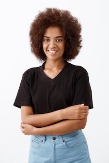 Linda garota africana sorrindo sobre parede de luz.