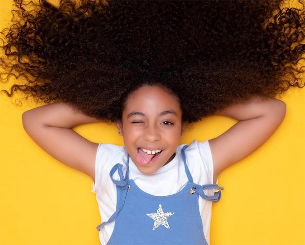 Linda garota afro-americana com cabelo encaracolado sorri e mostra a língua de fora