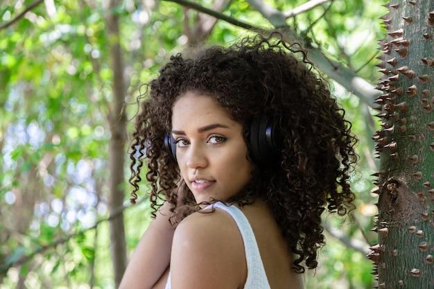 Linda garota afro-americana com cabelos cacheados no parque.