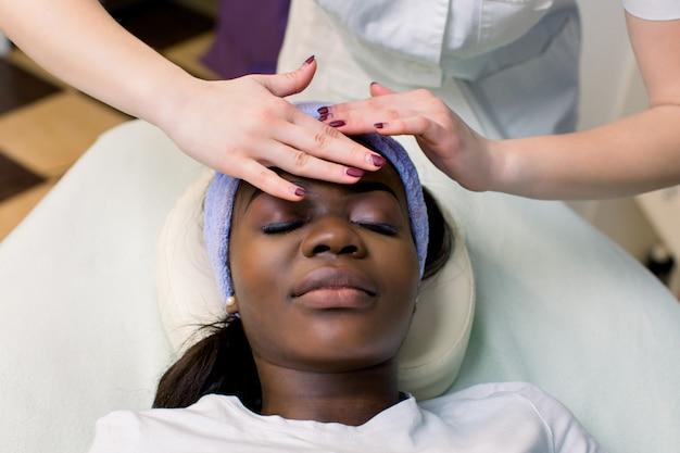 Linda garota afro-americana com massagem facial com os olhos fechados no salão spa