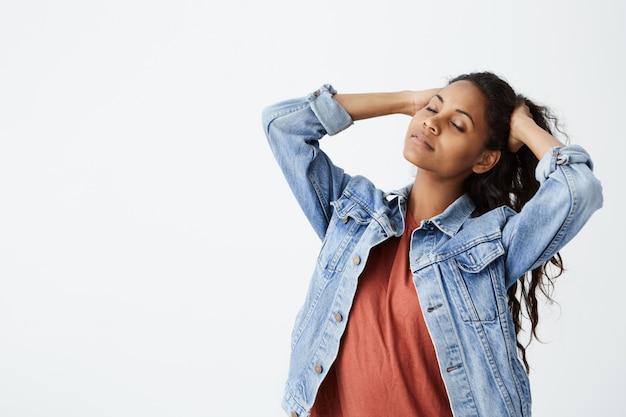 Linda garota afro-americana na jaqueta jeans com os olhos fechados, brincando com seus longos cabelos ondulados escuros. jovem mulher posando na parede branca.