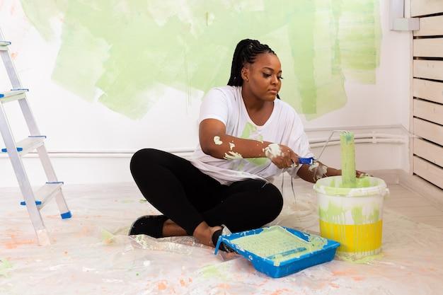 Linda garota afro-americana pintando a parede com rolo de pintura. retrato de uma jovem bonita
