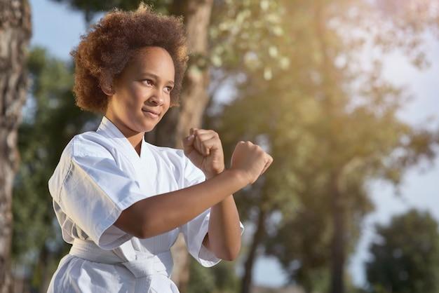 Linda garota afro-americana praticando artes marciais em um dia ensolarado no parque