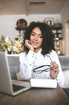 Linda garota afro-americana sentada no restaurante com o laptop e óculos na mão. menina bonita trabalhando em um café com notebook e laptop na mesa