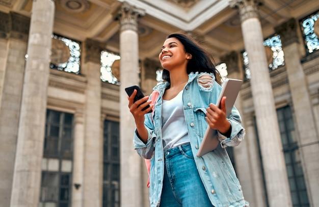 Linda garota afro-americana usa um smartphone com uma mochila e um laptop perto do campus.