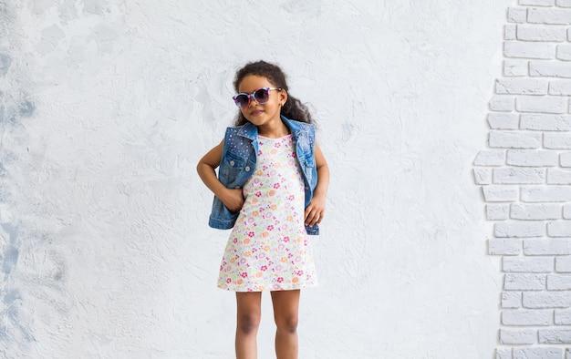 Linda garota afro contra a parede cinza