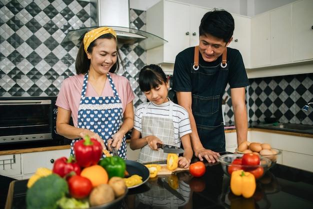 Linda garota ajudar seus pais estão cortando legumes e sorrindo ao cozinhar juntos na cozinha