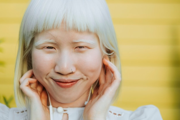 Linda garota albina ouvindo sua música favorita com fones de ouvido