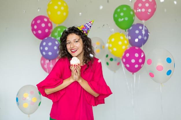 Linda garota alegre bonita com um bolo festivo ri e lança confete no fundo de balões coloridos