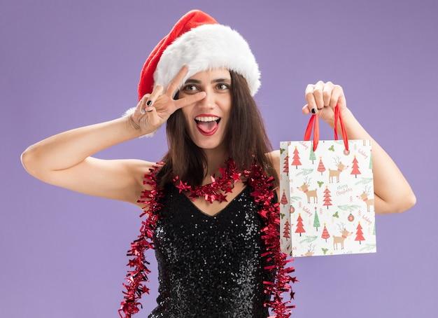 Linda garota alegre com chapéu de natal com guirlanda no pescoço, segurando uma sacola de presente, mostrando um gesto de paz isolado no fundo roxo