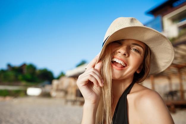 Linda garota alegre com chapéu engraçado repousa na praia de manhã