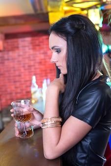 Linda garota alegre com coquetel no bar, em uma festa.