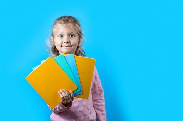 Linda garota alegre com covinhas nas bochechas e cabelos cacheados, segurando os cadernos coloridos da escola em azul
