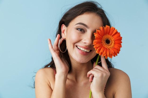 Linda garota alegre com roupas de verão, isolada sobre o azul, posando com uma flor herbera