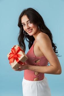Linda garota alegre com roupas de verão, isolada sobre o azul, segurando uma caixa de presente