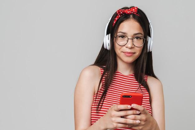 Linda garota alegre e alegre, vestindo roupa casual, em pé, isolada na parede cinza, ouvindo música com fones de ouvido, usando o telefone celular