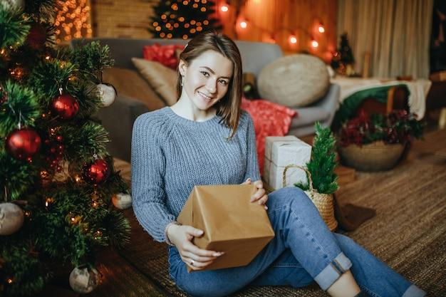 Linda garota alegre e feliz com presentes de natal no chão perto da árvore de ano novo em casa