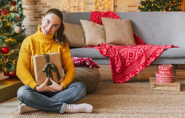Linda garota alegre e feliz com presentes de natal no fundo de uma árvore de ano novo em casa