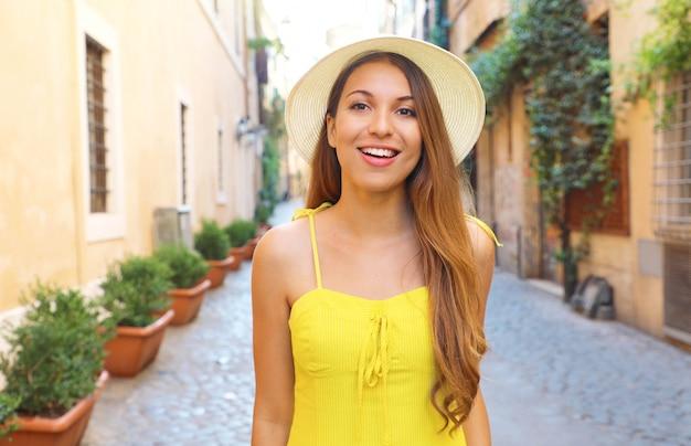 Linda garota alegre em trastevere, roma. feliz moda mulher com vestido amarelo e chapéu caminha pelas ruas de roma, itália.