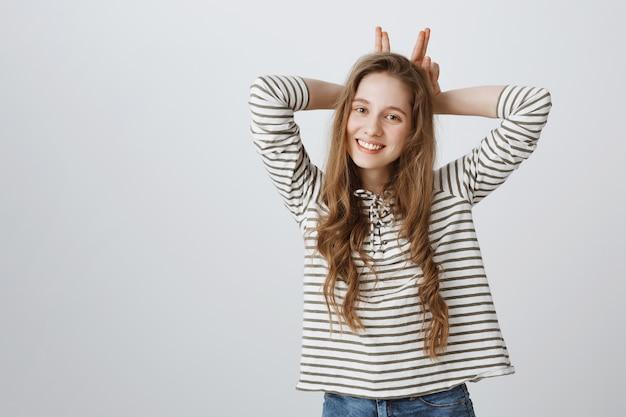 Linda garota alegre mostrando gesto de orelhas de coelho e sorrindo fofo