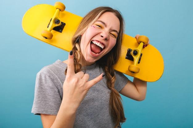 Linda garota alegre parada isolada, segurando um skate