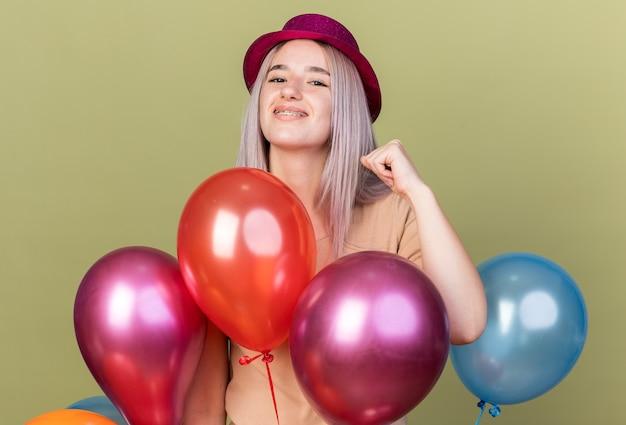 Linda garota alegre usando aparelho dentário com chapéu de festa atrás de balões mostrando um gesto de sim