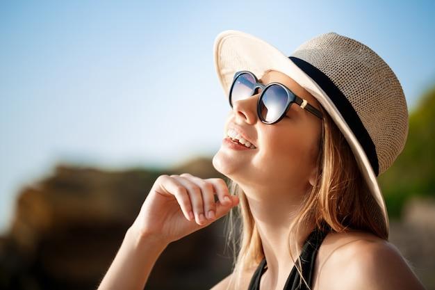 Linda garota alegre vestindo óculos e chapéu baseia-se na praia de manhã