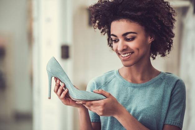 Linda garota americana está escolhendo sapatos de salto alto.