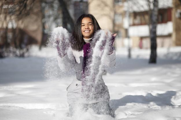Linda garota americana sorridente, sentado na neve, brincando ao ar livre com neve
