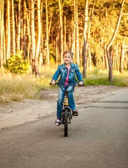Linda garota andando de bicicleta na estrada na floresta