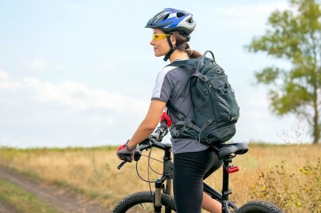 Linda garota andando de bicicleta na natureza