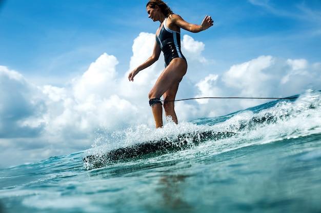 Linda garota andando em uma prancha de surf nas ondas