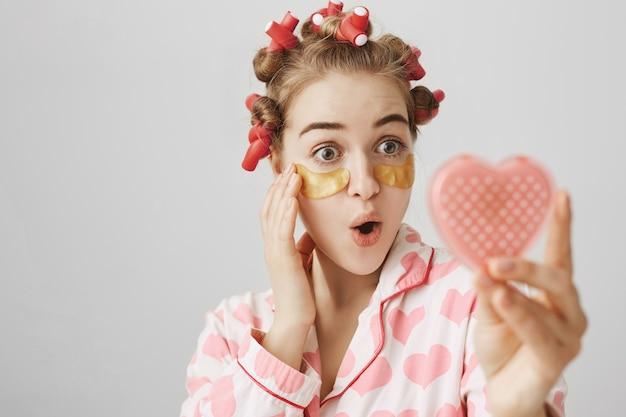 Linda garota animada com rolos de cabelo e tapa-olhos se olhando no espelho