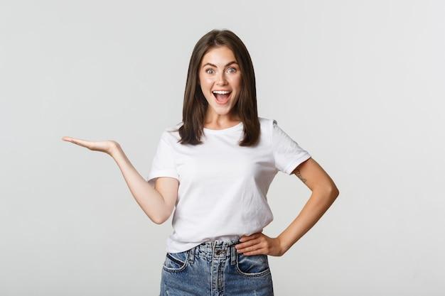 Linda garota animada estendendo o braço, segurando algo na mão e parecendo feliz no branco