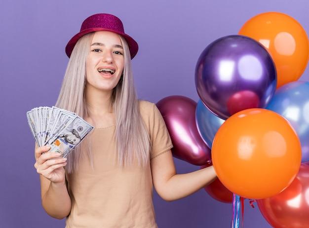 Linda garota animada usando aparelho dentário e chapéu de festa segurando balões com dinheiro isolado na parede azul