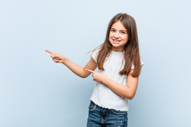 Linda garota animado apontando com o dedo indicador fora.