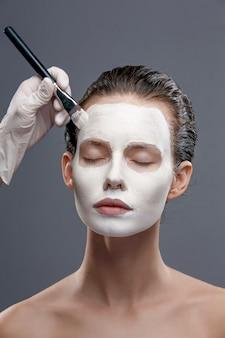 Linda garota aplicando uma máscara cosmética branca de pontos pretos
