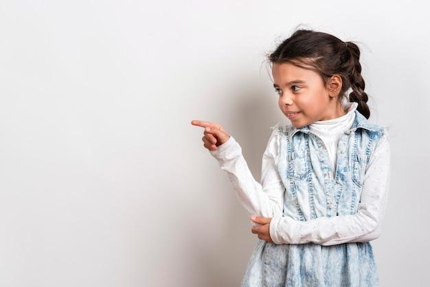 Linda garota apontando com cópia-espaço