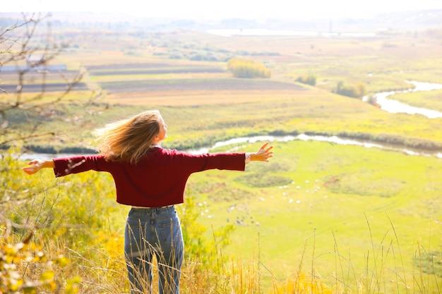 Linda garota, apreciando a vista da natureza. hipster na colina. rio e campo abaixo. estação do outono. mulher elegante ao ar livre. conceito turístico. viaje, descubra o mundo.