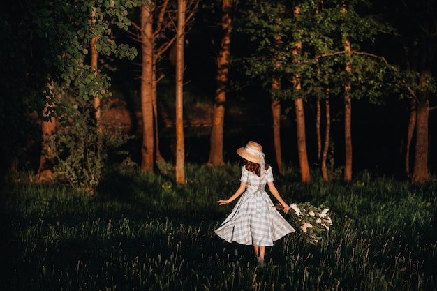 Linda garota, apreciando o cheiro de lilás num dia de verão. conceito de aromaterapia e primavera. uma menina bonita, uma linda mulher em um vestido azul longo vintage está de pé em um jardim lilás. jardinagem.