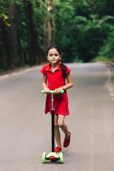 Linda garota, apreciando o passeio em scooter de impulso