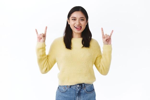 Linda garota asiática animada se divertindo em um show incrível, fazendo gestos de rock-n-roll e mostrando a língua sorrindo despreocupada, dançando ao som de música legal, parede branca de pé