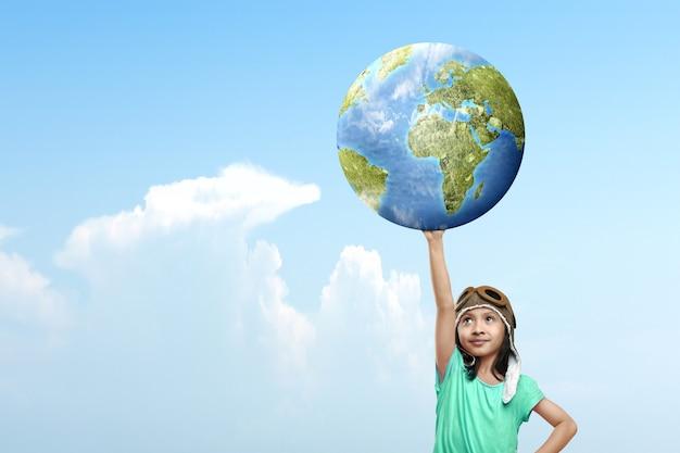 Linda garota asiática com boné de aviador segurando a terra com um céu azul