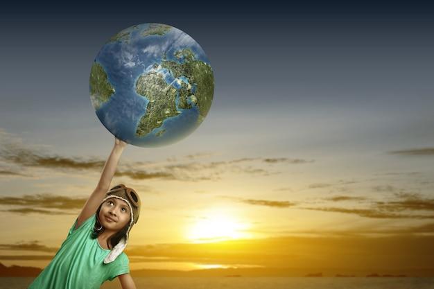 Linda garota asiática com boné de aviador segurando a terra e o céu ao pôr do sol